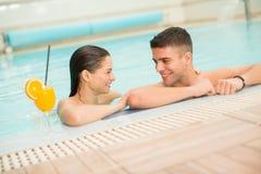 Het jonge paar ontspannen in de pool Stock Foto