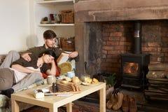 Het jonge paar ontspannen door brand Stock Afbeeldingen