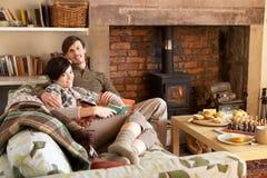Het jonge paar ontspannen door brand Royalty-vrije Stock Afbeeldingen