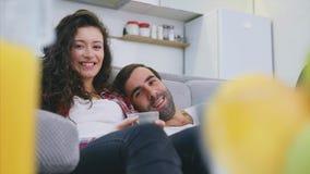Het jonge paar ontspannen in hun flat, het liggen op de laag en het letten van de op film stock footage