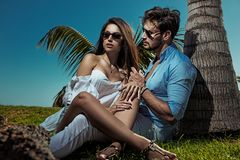 Het jonge paar ontspannen naast de palm Royalty-vrije Stock Foto's