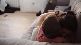 Het jonge paar ontspannen, omhelst en heeft pret die op de bank in de woonkamer met zolderbinnenland liggen Het spreken aan elk stock videobeelden