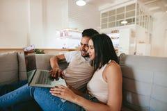 Het jonge paar ontspannen op laag met laptop Stock Foto's