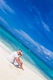 Het jonge paar ontspannen op zand tropisch strand op blauwe hemel Stock Fotografie