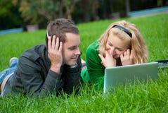 Het jonge paar ontspant en luistert aan muziek Stock Afbeeldingen