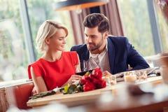 Het jonge paar op datum in restaurantzitting het drinken wijn juicht het bekijken elkaar toe offerte stock foto