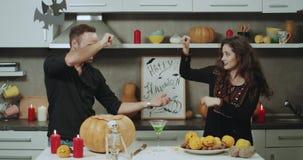 Het jonge paar spelen grappig op de keuken vóór een Halloween-nacht, heeft een goede stemming en mooie gezichten stock video