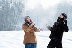 Het jonge paar spelen met sneeuw Stock Foto's