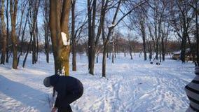 Het jonge paar spelen in openlucht in de sneeuw stock footage