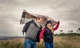 Het jonge paar spelen in openlucht met deken in a Royalty-vrije Stock Afbeeldingen