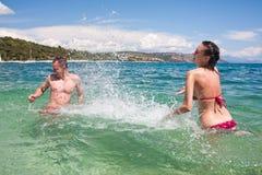 Het jonge paar spelen in water Royalty-vrije Stock Afbeeldingen