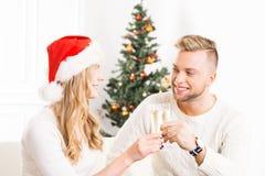 Het jonge paar stellen naast een Kerstboom Stock Foto