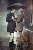 Het jonge paar stellen in zware regen Stock Foto