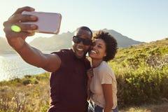 Het jonge Paar stelt voor Vakantie Selfie op Clifftop stock afbeelding