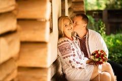 Het jonge paar in traditionele Oekraïense kleren kuste op de achtergrond van oude Oekraïense architectuur stock afbeeldingen