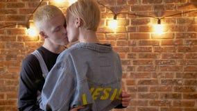 Het jonge paar van hipsters gooit koppen en kussen, hartstocht, het lachen, liefdeconceptie, baksteenachtergrond weg stock footage