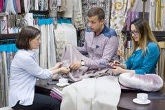 Het jonge paar van kleine bedrijfseigenaars van de bespreking van de stoffenopslag en adviseert de koper stock foto