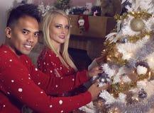 Het jonge paar verfraait thuis een Kerstboom Stock Fotografie