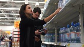 Het jonge paar vergelijkt twee flessen water onder zich stock footage