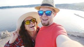 Het jonge paar wandeling nemen selfie Gelukkige jonge man en vrouw die zelfportret in de bergen nemen stock video