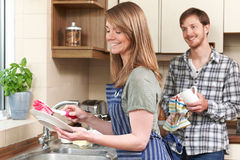 Het jonge Paar Wassen omhoog bij Gootsteen samen Stock Afbeelding