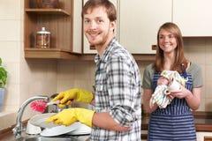Het jonge Paar Wassen omhoog bij Gootsteen samen Royalty-vrije Stock Fotografie
