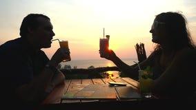 Het jonge paar zit in een strandkoffie die het overzees overzien en zonsondergang verbazen, die glazen met cocktails clinking Lan stock footage