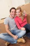 Het jonge paar zit op de vloer houdend zeer belangrijke in hand Royalty-vrije Stock Afbeelding