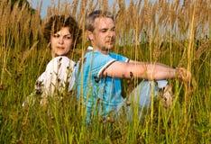 Het jonge paar zit op een gras Stock Fotografie