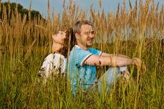 Het jonge paar zit op een gras Stock Afbeeldingen