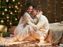 Het jonge paar zit op vloer in donker houten binnenland met lichten Romantisch avond en liefdeconcept De vakantie van het nieuwja stock foto's