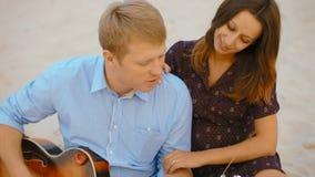 Het jonge paar zit op zand op strand spelend de gitaar, het zingen en het glimlachen stock footage