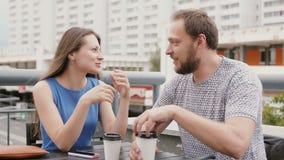 Het jonge paargesprek in een koffie op de straat, een vrouw emotioneel vertelt iets aan de man 4K stock footage