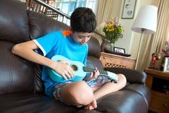 Het jonge pan Aziatische jongen praktizeren op zijn blauwe ukelele in een huismilieu royalty-vrije stock afbeelding