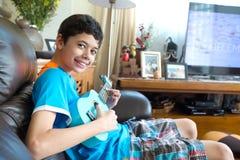 Het jonge pan Aziatische jongen praktizeren op zijn blauwe ukelele in een huismilieu Stock Afbeeldingen