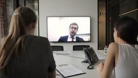 Het jonge personeel is op online conferentie in modern bureau stock video