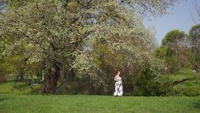 Het jonge reizigers zwangere vrouw lopen, lopend, zich omdraait en geniet van haar vrije tijdsvrije tijd in een park met stock video