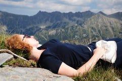 Het jonge rode haired vrouw ontspannen op de achtergrond van hooggebergte stock afbeeldingen