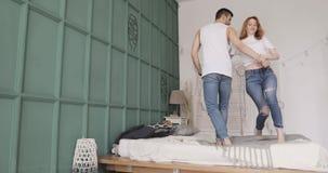 Het jonge romantische paar danst, glimlacht en het flirten bevindt zich in bed Verhouding en liefdeconcept stock footage