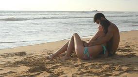 Het jonge romantische paar geniet van mooie meningszitting op het strand en het koesteren Een vrouw en een man zitten samen binne stock footage