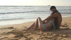 Het jonge romantische paar geniet van mooie meningszitting op het strand en het koesteren Een vrouw en een man zitten samen binne stock video
