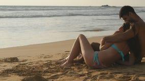 Het jonge romantische paar geniet van mooie meningszitting op het strand en het koesteren Een vrouw en een man zitten samen binne stock videobeelden