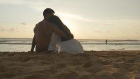 Het jonge romantische paar geniet van mooie zonsondergangzitting op het strand en het koesteren Een vrouw en een man zitten samen stock videobeelden
