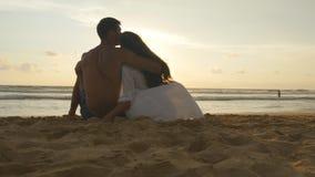 Het jonge romantische paar geniet van mooie zonsondergangzitting op het strand en het koesteren Een vrouw en een man zitten samen stock video