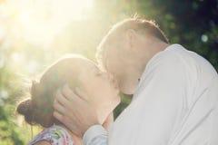 Het jonge romantische paar kussen in zonneschijn Uitstekende liefde Stock Afbeelding