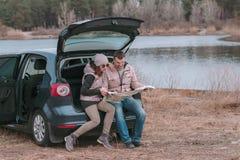 Het jonge romantische paar zit in open boomstam van auto dichtbij de de rivier en het letten op wegenkaart stock afbeelding