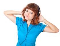 Het jonge roodharige meisje luistert aan muziek en dans Stock Fotografie