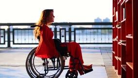 Het jonge Roodharige Meisje met een Handicap in Oranje Kleding trekt op een Rolstoel uit aan het Boekenrek en neemt het Boek stock footage