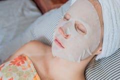 Het jonge roodharige vrouw ontspannen op een bed Bladmasker op haar gezicht royalty-vrije stock foto's