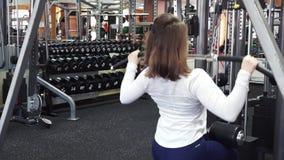 Het jonge schitterende atletische wijfje voert achterspieroefeningen op pulldown de machine van de baroefening in gymnastiek uit stock videobeelden
